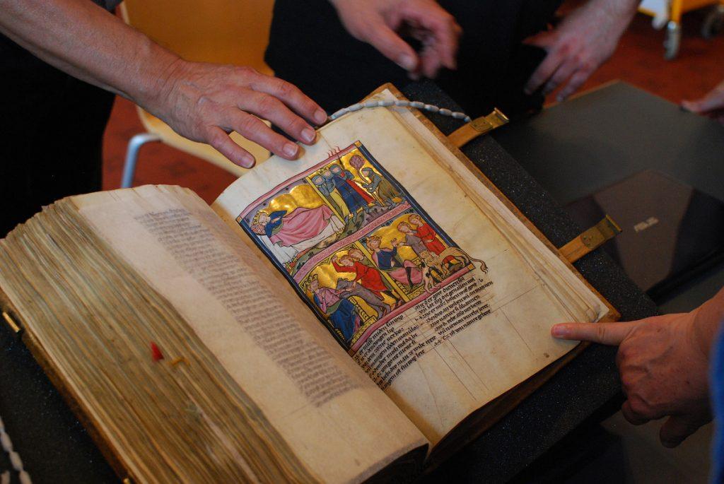 A view of the manuscript, St. Gallen, Kantonsbibliothek, Vadianische Sammlung, VadSlg Ms. 302, part 2, fol. 25r, with people's hands around